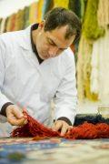 Fachmann sucht neue Wolle für Teppichreparatur aus